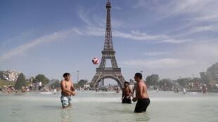 Des Parisiens se baignent dans la fontaine du Trocadéro, face à la Tour Eiffel.