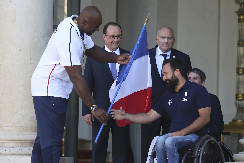 O boxeador francês medalha de ouro nos Jogos do Rio, Teddy Riner, passa a bandeira francesa ao tenista Michael Jeremiasz, porta-bandeira francês na Paralimpíada, em imagem desta terça-feira, 23 de agosto de 2016.