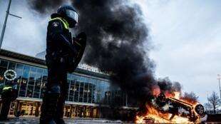 Une voiture brûle devant la gare de Eindhoven aux Pays-Bas, le 24 janvier 2021.