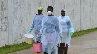 Mulheres em um centro de isolamento em Monróvia, Libéria, carregam produtos usados para desinfetar as instalações.
