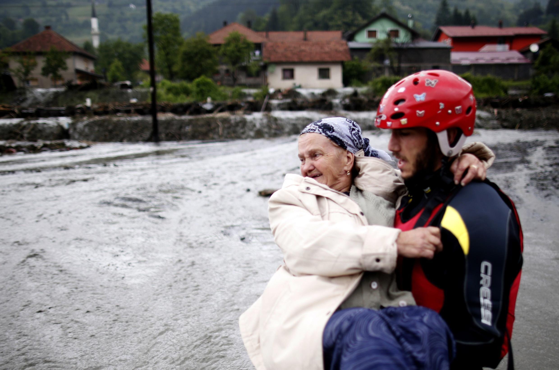 Mulher é socorrida em cidade da Bósnia,  onde as enchentes já afetaram um quarto dos habitantes do país.