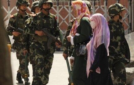 Tân Cương : Phụ nữ mang khăn choàng  không được sử dụng phương tiện chuyên chở công cộng. Ảnh AFP