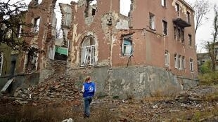 A local WFP (World Food Programme) worker is standing in front of a shelled house in Kramatorsk, Ukraine.