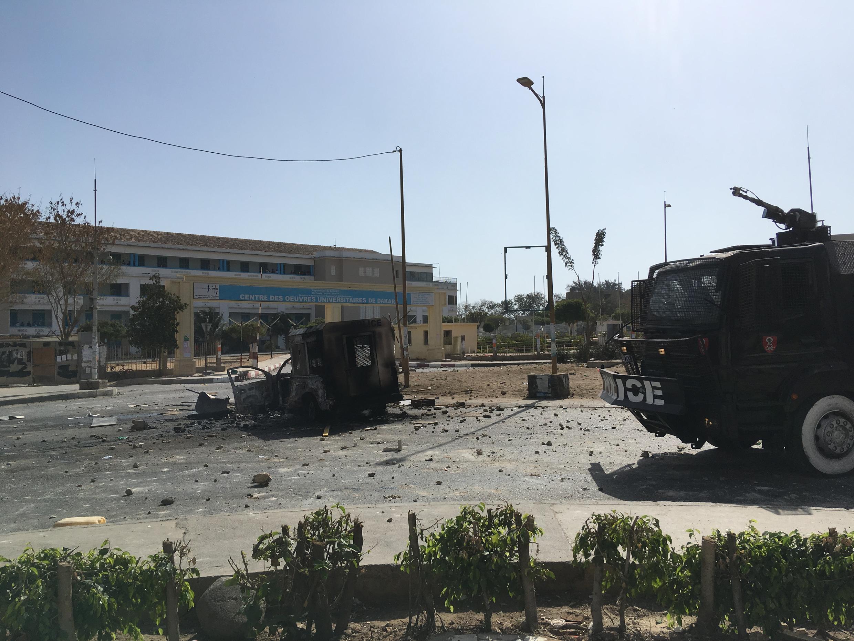 En dehors de l'université, une voiture de police carbonisée et des débris jonchent le sol.
