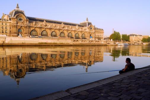 Face au Musée d'Orsay, un pêcheur tente d'attraper un poisson avec sa canne...