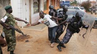 Maafisa wa usalama jijini Kampala, wakimkabili mfuasi wa Kizza Besigye hivi karibuni