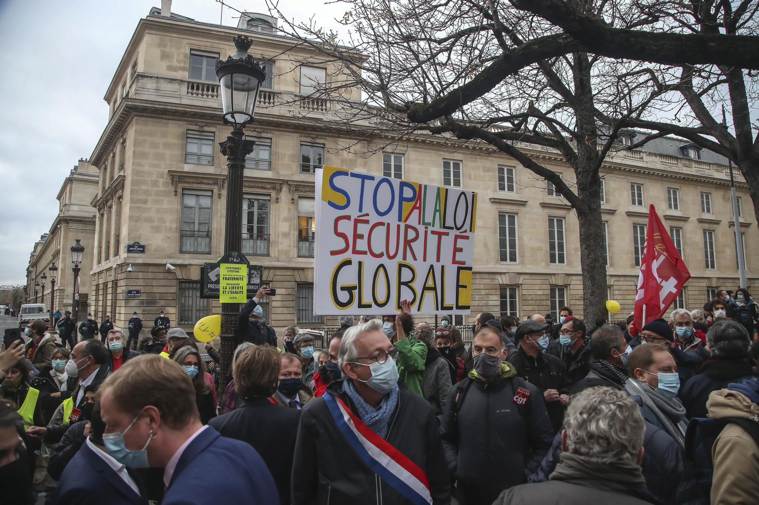 """A protester holds a sign calling for a proposed """"global security"""" law to be scrapped at a rally in Paris last November. MPs are to vote on the final version of the proposals on Thursday, though it will most likely be reviewed by constitutional officials before becoming law."""