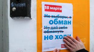 Des activistes et partisans du leader de l'opposition Alexeï Navalny collent des flyers dans l'entrée d'un immeuble à Moscou, le 10 février 2018, appellant au boycott de la présidentielle.