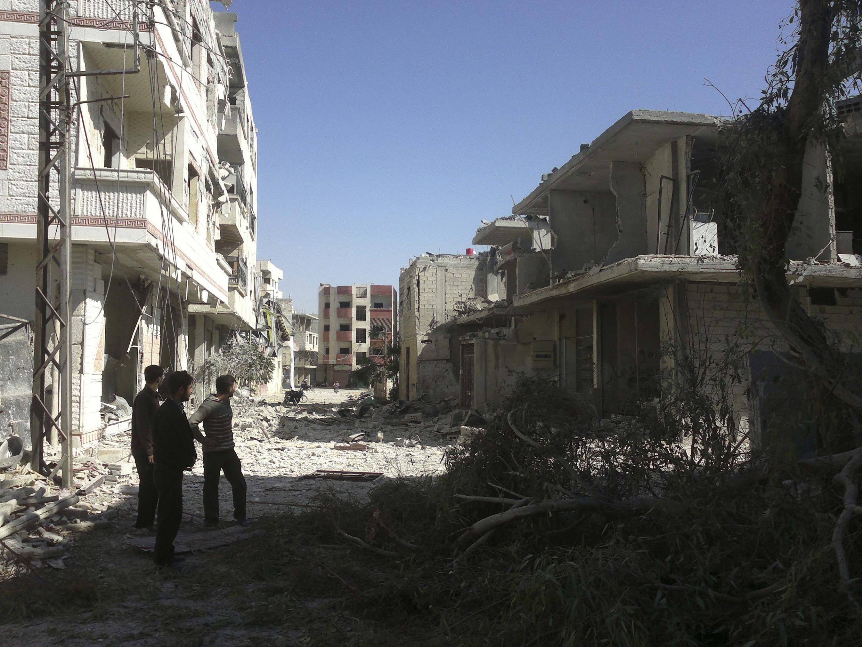 População observa estragos após bombardeio em Erbeen, perto de Damasco, na Síria.