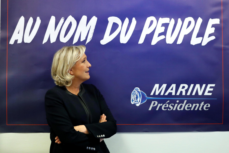 """Marine Le Pen posa em frente a um dos seus cartazes de campanha para 2017, que diz """"em nome do povo""""."""