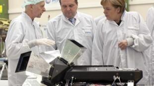 La chancelière allemande Angela Merkel (d) et Stefan Mappus (c), gouverneur du Baden-Wuerttemberg, lors de leur visite à Astrium, filiale du groupe EADS, à Immenstaad, le 23 février 2011.