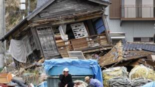 Một ngư dân Nhật Bản đang cố vá lại tấm lưới, trước căn nhà đổ nát tại Otsu, cách Fukushima 70km.