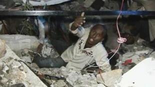 Un homme, coincé sous des décombres, appelle à l'aide dans les rues de Port-au-Prince le 13 janvier