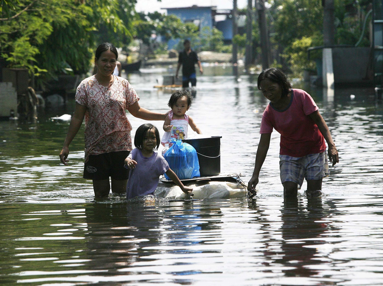 Habitantes de Manila tentam salvar seus pertences das enchentes que tomaram a capital.