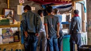 Calais, le 12 août 2016. Des migrants font la queue dans une petite alimentation de fortune.