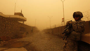 A US Army soldier stands guard during a sand storm in his base in Kandahar