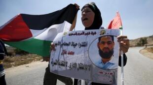 Palestina segura cartaz com a imagem de Mohammed Allan na Faixa de Gaza, em foto de 14 de agosto de 2015.