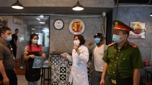 Thanh tra y tế cùng công an kiểm tra vệ sinh tại một quán ăn ở Hà Nội, Việt Nam, ngày 25/05/2021.