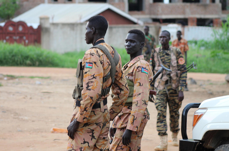 Des soldats et policiers sud-soudanais montent la garde dans une rue à Juba, le 10 juillet, alors que des violences frappent la capitale.