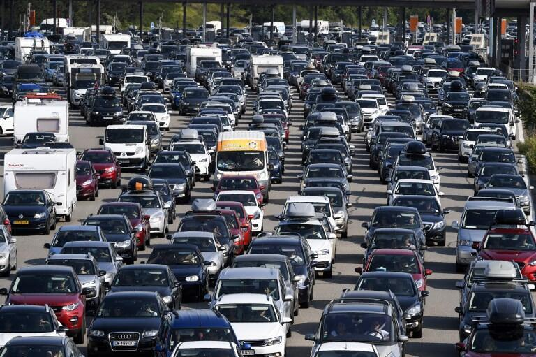 Motorists queue in their vehicles at a toll station on the A7 motorway near Vienne, south-east France on Saturday