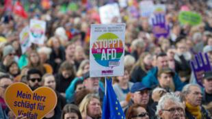 Un manifestant tient une pancarte où l'on peut lire: «Stop à l'AFD», pour protester contre ce parti politique d'extrême droite.