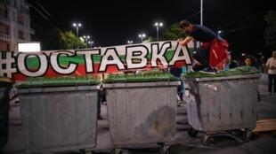 Un manifestant bulgare fixe une banderole «Démission» sur une nouvelle barricade faite de poubelles sur une grande artère de Sofia, le 7 août 2020.