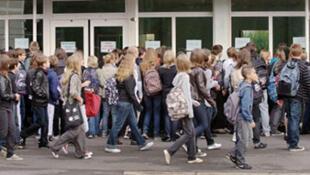 Des élèves du collège Jean Mermoz regardent la liste d'affectation et de la composition des classes, le 2 septembre 2009 près de Lille.