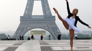 """Một nữ nghệ sĩ ba lê trình diễn trước tháp Eiffel đã được tổ chức Greenpeace bất ngờ giăng biểu ngữ """"Tự do, Bình đẳng, Bác ái"""" để kêu gọi chống đảng Mặt Trận Quốc Gia, ngày 05/05/2017."""