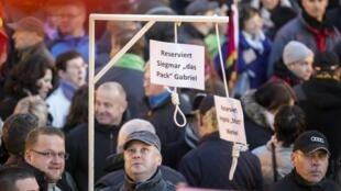 """Na manifestação organizada pelo movimento Pegida na última segunda-feira (12), participantes carregaram forcas com as mensagens: """"Reservado para Sigmar Gabriel  e Angela Merkel""""."""
