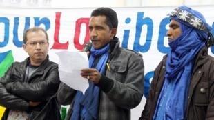 Moussa Ag Assarid (d), porte-parole du MNLA du Mali et Irij Maouche (g), membre de l'association Tamazgha écoutent le représentant du MNLA à Paris, Mossa Ag Attahe, lors d'une manifestation à Paris, en faveur de l'indépendance de l'Azawad, le 7 avril 2012