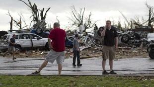 Habitantes de Joplin junto a vehículos dañados por el tornado, el 22 de mayo de 2011.