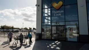 Passants devant une agence Thomas Cook, à Peterborough, dans le centre de l'Angleterre, après la faillite du voyagiste.