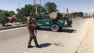 Un membre des forces armées afghanes surveillent le lieu d'un attentat-suicide sur un convoi militaire à Kaboul le 31 mai 2019.
