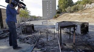 Um cinegrafista filma os restos de um acampamento cigano cujos habitantes foram expulsos por moradores de Marselha.