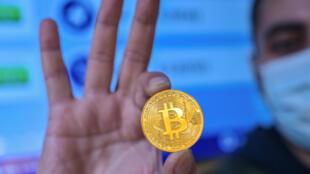 Un hombre sostiene una imitación física de un bitcóin, en Estambul, Turquía, el 17 de diciembre de 2020