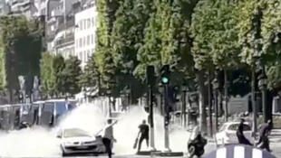 French police officers engage with a suspect on the Champs Elysees - image from social media