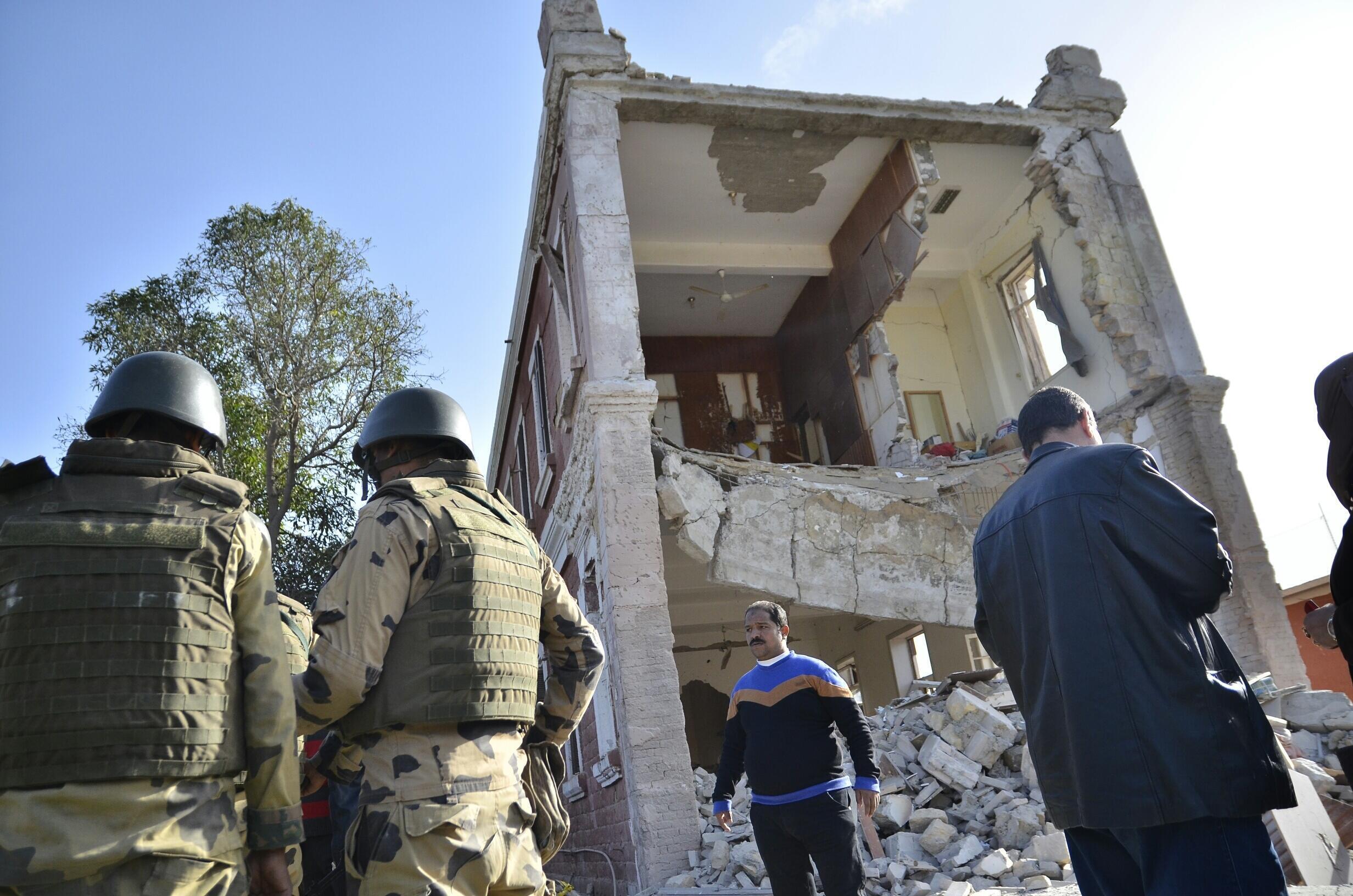 Des soldats égyptiens devant un bâtiment des renseignements militaires détruit par une explosion, à l'est du Caire, le 29 décembre 2013.