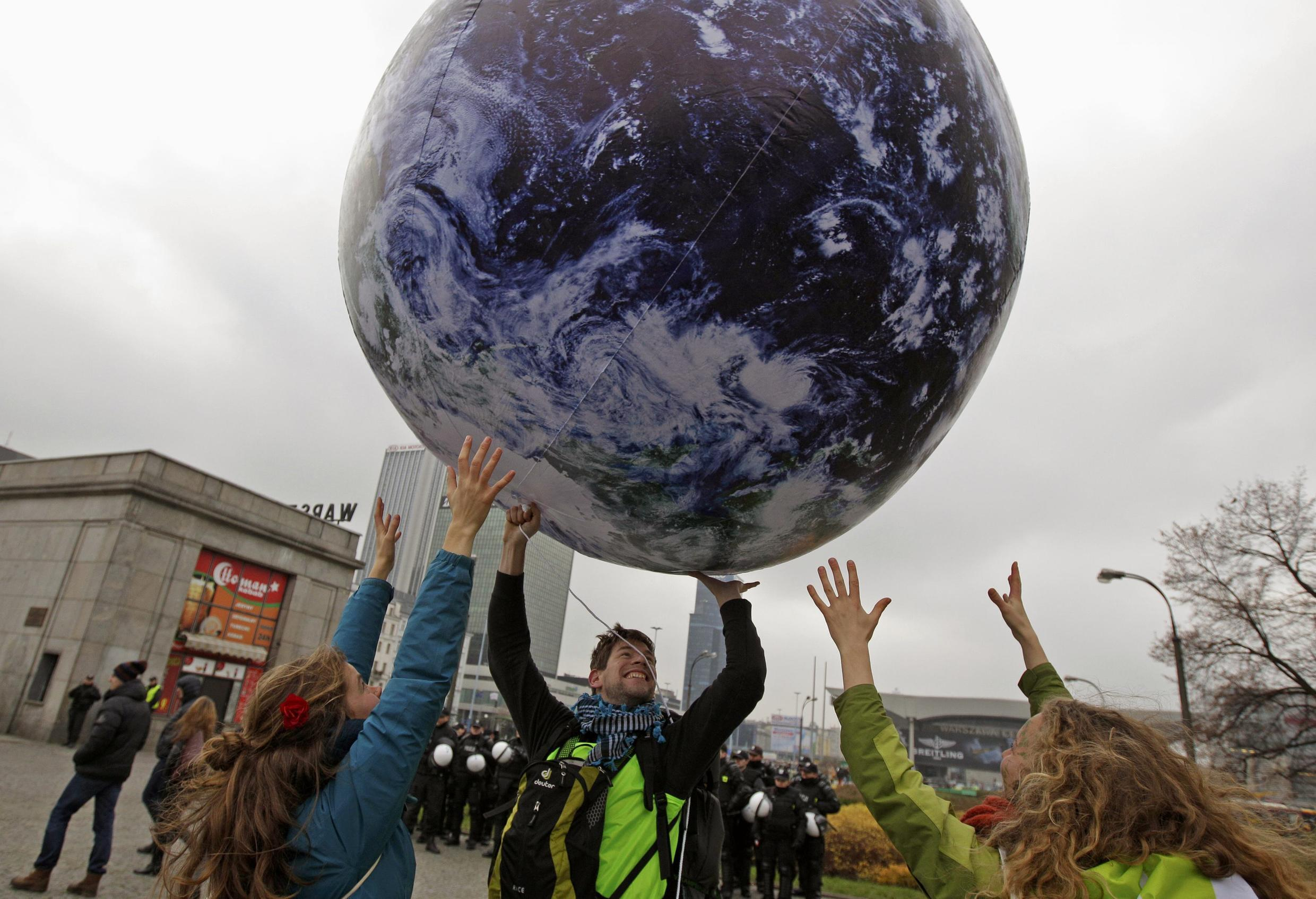 Environmental activists play with a giant globe on the streets in a rally demanding more action to battle climate change during the 19th conference of the United Nations Framework Convention on Climate Change