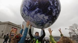 Militantes juegan con un globo terráqueo gigante, en Varsovia.