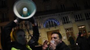Manifestantes em frente ao teatro Bouffes du Nord, em Paris, pedem a demissão de Emmanuel Macron.