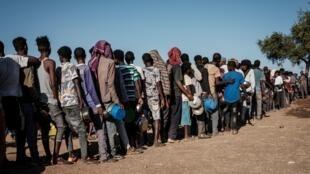 Refugiados etíopes, que huyeron del conflicto en la región del Tigré, hacen fila para recibir alimentos distribuidos por Muslim Aid en el campo de refugiados de Um Raquba, en Sudán, el 12 de diciembre de 2020