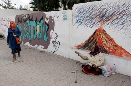 Une femme demande l'aumône dans une rue de Sidi Bouzid le 11 décembre 2012,  ville où Mohamed Bouazizi s'est immolé par le feu il y a deux ans.