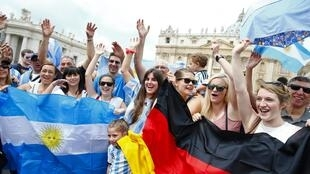 Болельщики держат флаги Германии и Аргентины в ожидании воскресной молитвы папы римского Франциска на площади святого Петра в Ватикане, 13 июля 2014 г.