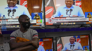 A man stands inside an electronics shop in Nairobi as President Kenyatta gives an address in July 2020, announcing measures against Covid-19.