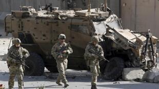 Des soldats de l'Otan se tiennent à proximité d'un de leurs véhicules détruits, à Kaboul, en Afghanistan, le 11 octobre 2015.