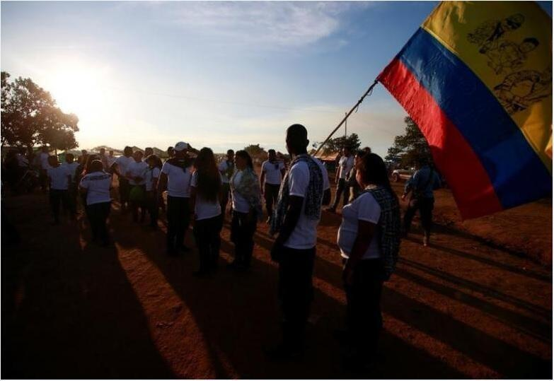 Fighters from the Revolutionary Armed Forces of Colombia (FARC), are seen with the Colombian flag at the camp where they will ratify a peace deal with the government, near El Diamante in Yari Plains, Colombia, September 22, 2016.