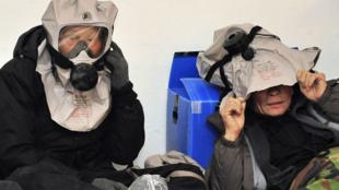 Civis sul-coreanos com mascáras de gás durante as manobras militares da Coreia do Sul, no dia 20 de dezembro.