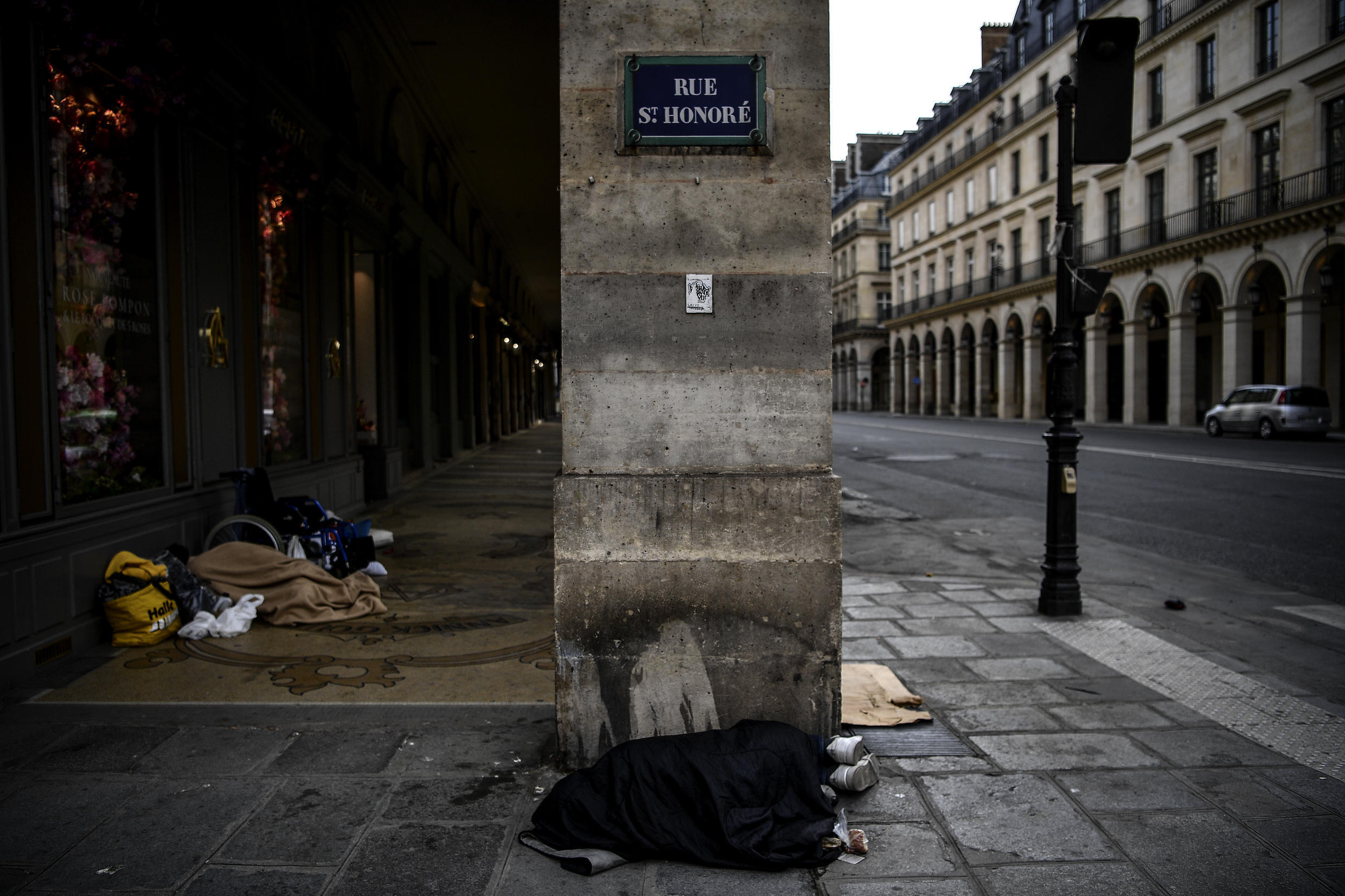 A homeless man sleeps on the pavement along rue St Honore in Paris on April 21, 2020.