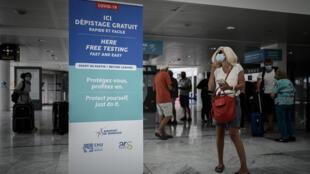 Una mujer con una máscara facial mira un cartel para una prueba gratuita de COVID-19 (nuevo coronavirus) que se muestra en la sala de llegadas del aeropuerto internacional de Burdeos-Merignac en Merignac, suroeste de Francia, el 23 de julio de 2020.