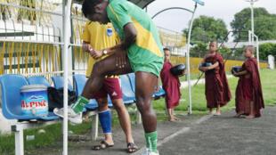 Des novices bouddhistes regardent un joueur du club de football Yadanarbon de Côte d'Ivoire se réchauffer avant une séance d'entraînement.